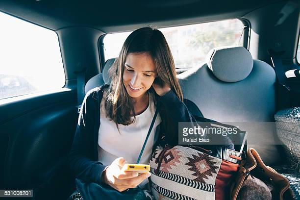 Pretty woman using smartphone in backseat of car