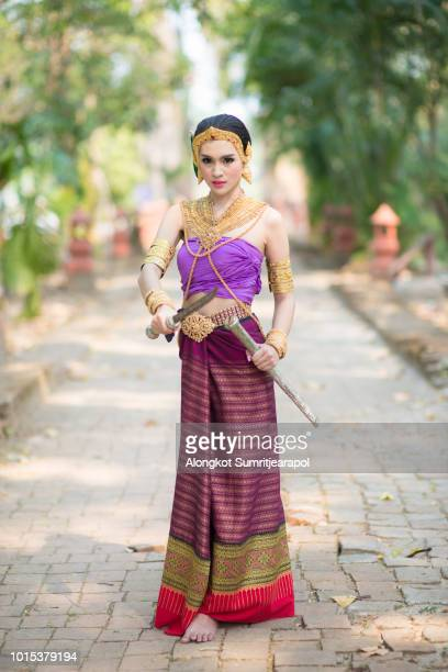 A Pretty woman wearing ancient Traditional Thai Costumes with sword posting like ancient thai warrior.