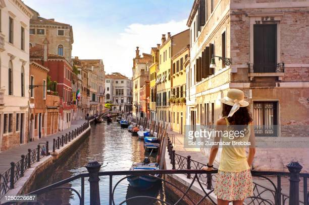 pretty woman wearing hat, yellow t-shirt and matching skirt standing on a small venice bridge looking down the canal of the venice lagoon - gondola traditional boat stock pictures, royalty-free photos & images