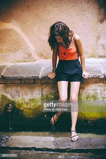 pretty woman wetting her feet at fountain - jelly shoe stock pictures, royalty-free photos & images