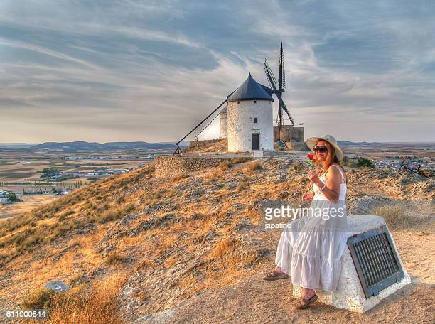 pretty woman with a rose looking at the windmills at sunset - トレド ストックフォトと画像