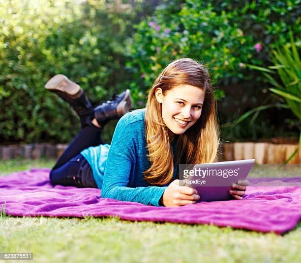 Hübsche Frau mit tablet PC auf dem Bauch liegen Decke im Garten
