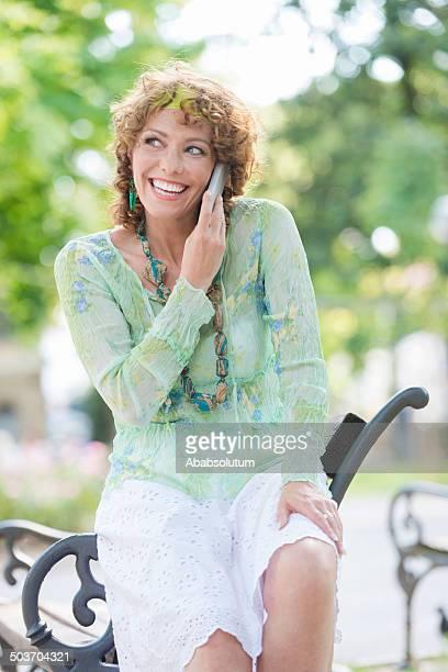 Jolie femme avec le téléphone sur un banc de parc de la ville, Italie, Europe