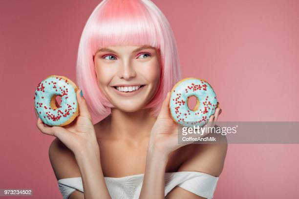 pretty woman with pink hairstyle holding multi-colored donuts - teen russia stock photos and pictures