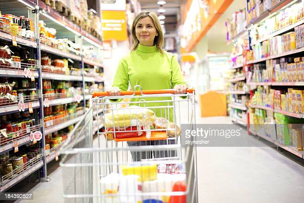 Hübsche Frau mit Einkaufswagen im Supermarkt gehen.