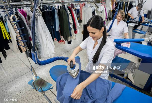 pretty woman working at a laundry service ironing clothes smiling - dry cleaner stock pictures, royalty-free photos & images