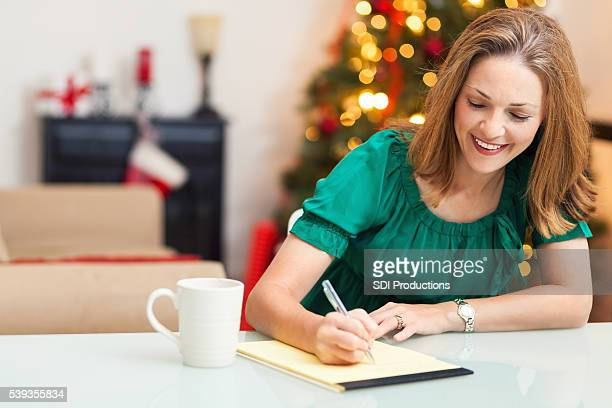 pretty woman writing letter at christmas - list stock pictures, royalty-free photos & images