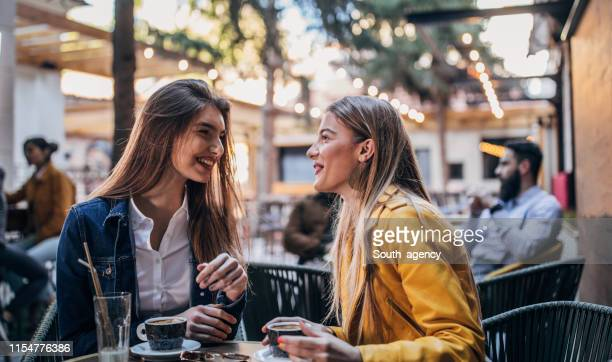 mooie vrouwen koffie drinken in een café tuin - patio stockfoto's en -beelden