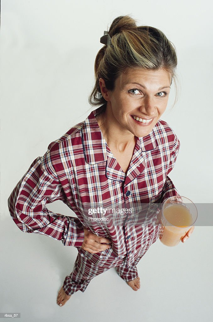 pretty young adult blonde caucasian female with her hair up is dressed in checkered red pajamasand is barefoot as she stands holding a glass of orange juice and smiles up at the camera humorously : Foto de stock