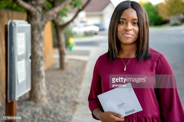 pretty young african american woman in her twenties exercising her american rights by voting by mail in an election - voting by mail stock pictures, royalty-free photos & images