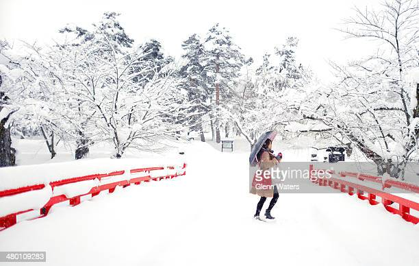 Pretty young asian lady tourist taking a photo of the beautiful snowy winter scean from a castle bridge in Hirosaki northern Japan.