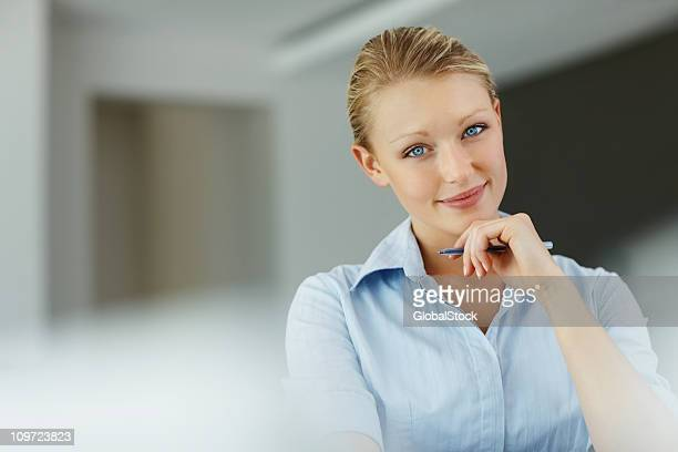 Pretty young business woman holding a pen