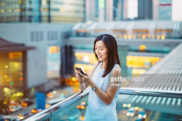 Pretty young businesswoman text messaging on smartphone cheerfully in city street