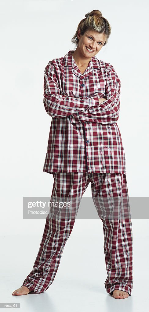 pretty young caucasian adult blonde female barefoot with hair up wearing red plaid pajamas stands with arms folded looking at the camera with a humorous smile : Foto de stock