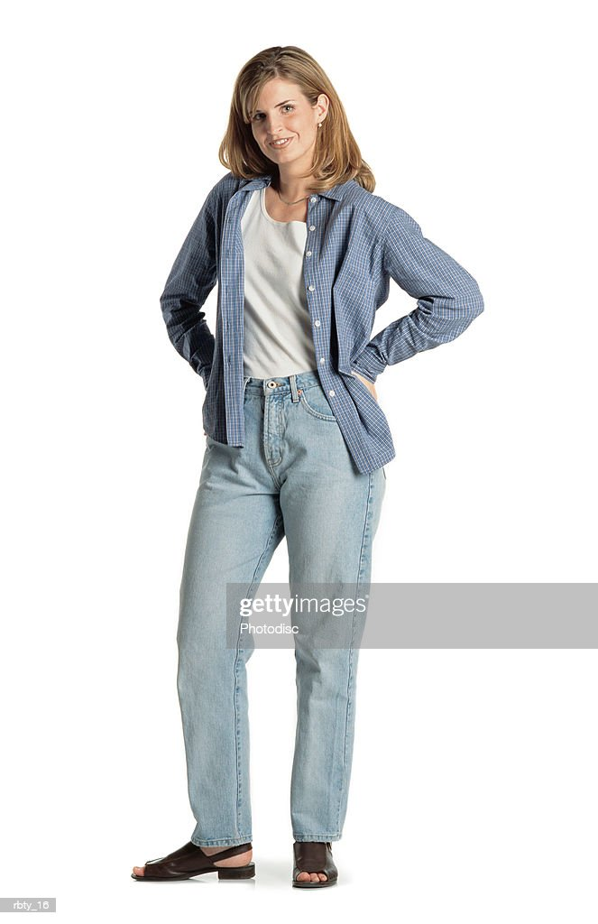 pretty young caucasian woman with long brown hair wearing a blue shirt sandals and blue jeans stands smiling at the camera with her hands on her hips and smiles : Foto de stock