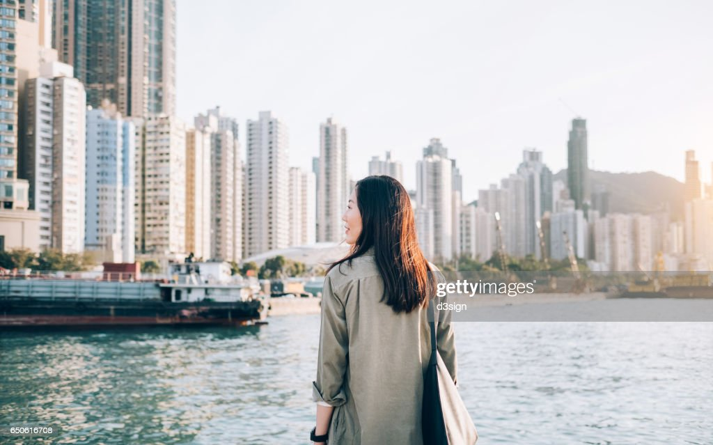 Pretty young girl enjoying the city view by the sea on a fresh morning : Stock Photo