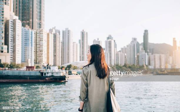 Pretty young girl enjoying the city view by the sea on a fresh morning
