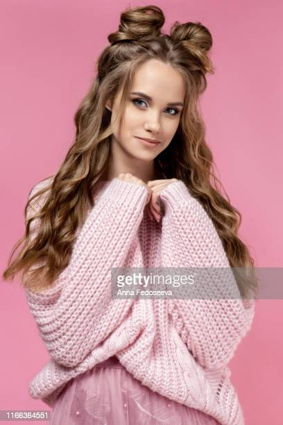 pretty young girl in a pink sweater on a pink background with a haircut and curly long hair. pink total look. fashionable, stylish, youth clothing. salon hairstyles, women barbershop and makeup. - actress photos stock pictures, royalty-free photos & images