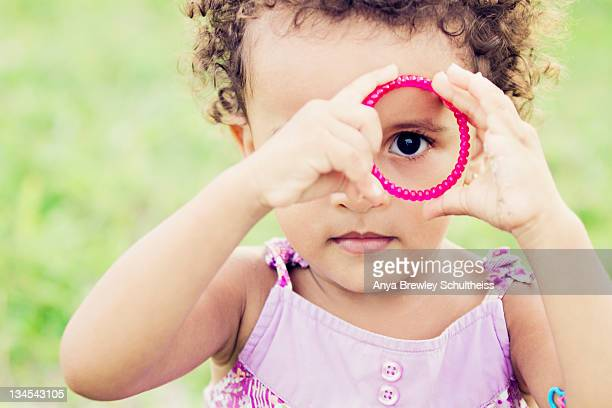 Pretty young girl looking through bracelet