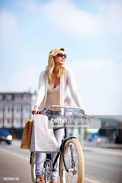 Pretty young girl riding a bicycle on the street