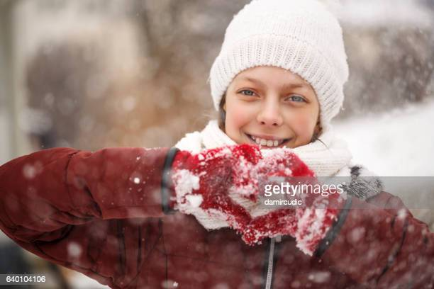 Pretty young girl with heart shaped hands in the gloves