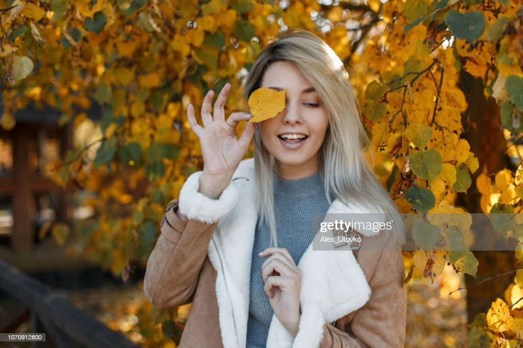 Pretty young happy girl model with blue eyes in a fashion jacket with fur covered her face with a yellow autumn leaf in the gold fall park . Beautiful smiling woman. : Stock Photo