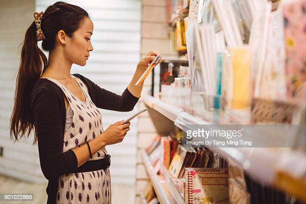 Pretty young lady choosing cards in shop