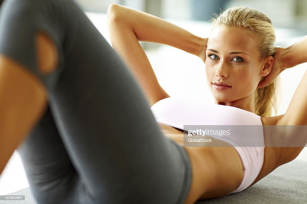 Pretty young lady doing abs exercise : Stock Photo