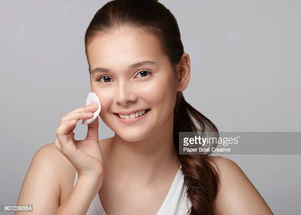 pretty young lady holding a cotton pad on her cheek, wiping away dirt and oil - pores stock photos and pictures