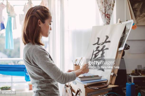 Pretty young lady practicing Chinese calligraphy at home.