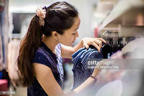 Pretty young lady shopping in a fashion boutique.