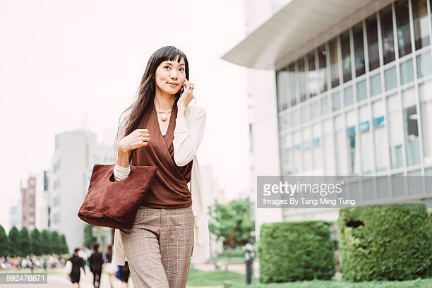 Pretty young lady taking on smartphone joyfully