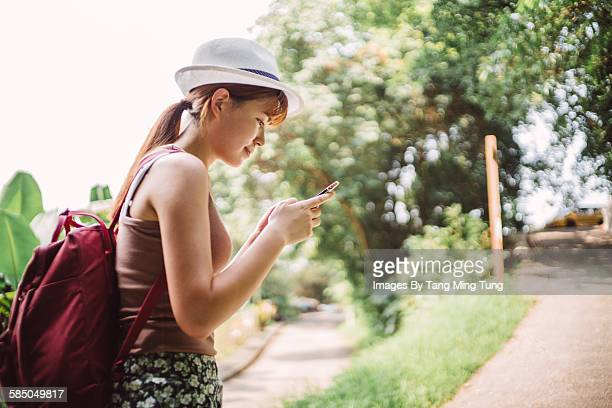 Pretty young lady travelling using GPS smartphone