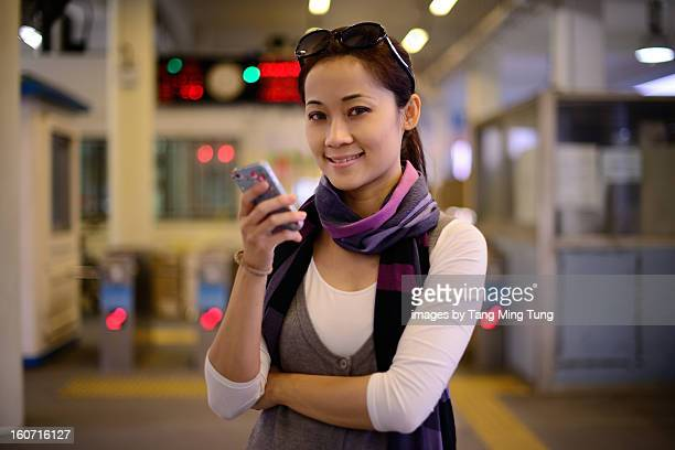 Pretty young lady using a smartphone at ferry pier
