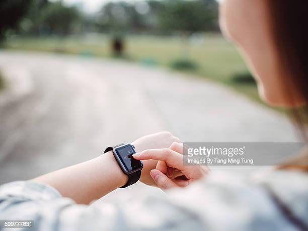 Pretty young lady using smart watch in the pathway