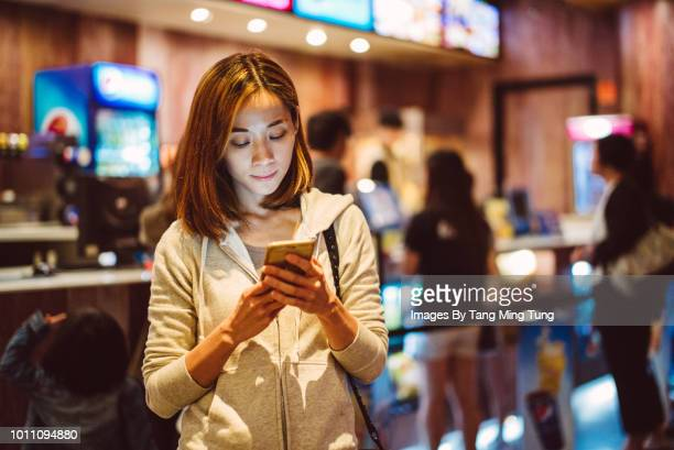 pretty young lady using smartphone in a cinema's box office / concession stand. - one night stand stock-fotos und bilder