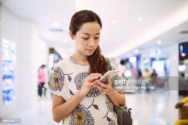 Pretty young lady using smartphone in a shopping mall.