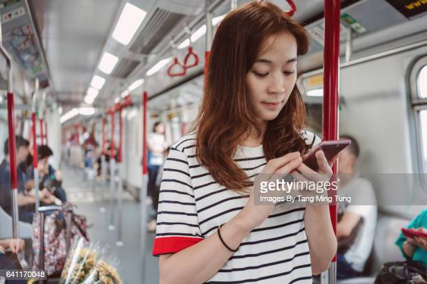 Pretty young lady using smartphone on a train
