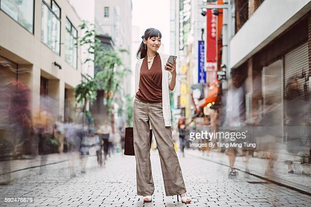 pretty young lady using smartphone on busy street - one mid adult woman only stock pictures, royalty-free photos & images