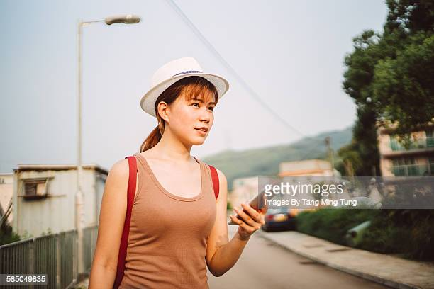 Pretty young lady using smartphone on roadside