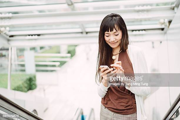 Pretty young lady using smartphone on the go
