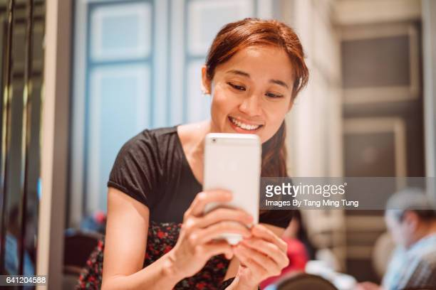 Pretty young lady using smartphone taking pictures in a restaurant joyfully.
