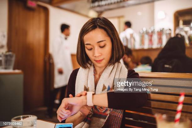 pretty young lady waiting and using her smartwatch joyfully in the restaurant - waiting stock pictures, royalty-free photos & images