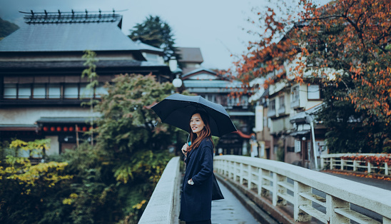 Pretty young lady walking along the old town and enjoying the scenics in a Japanese Zen Garden on a rainy day. - gettyimageskorea