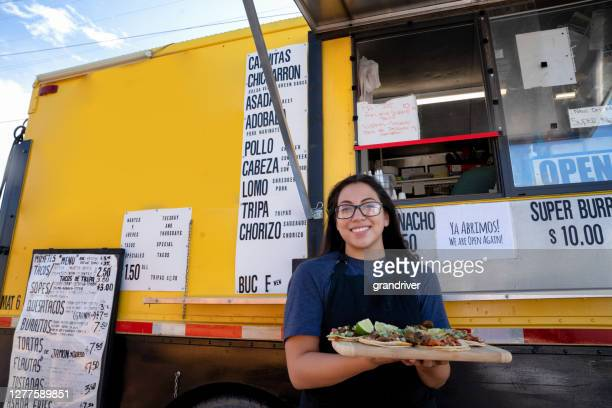 pretty young mexican woman in front of her small business food truck taco stand smiling at the camera and displaying a variety of her delicious gourmet tacos - serving food and drinks stock pictures, royalty-free photos & images
