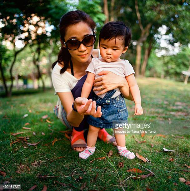 Pretty young mom and baby girl playing on the lawn