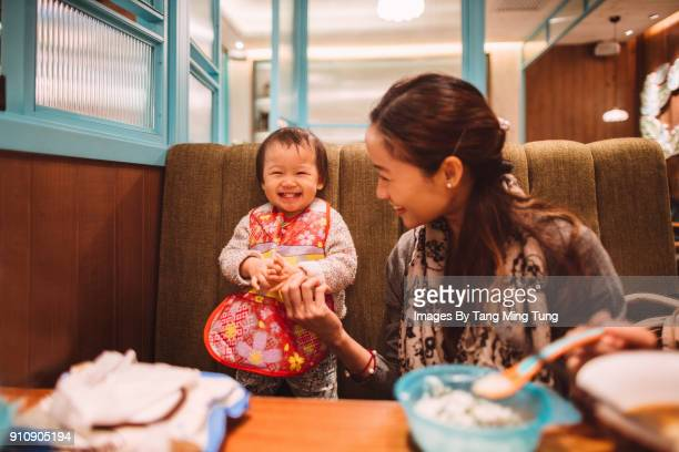 Pretty young mom and lovely baby having fun enjoying meal in a restaurant.