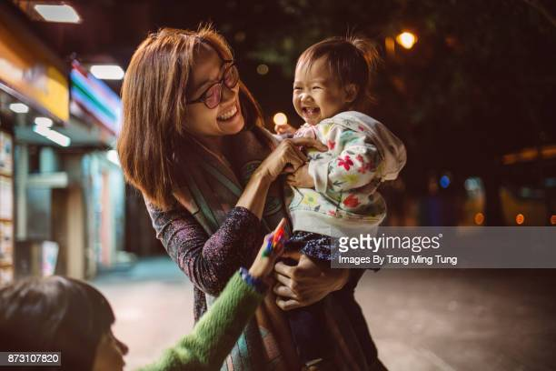 Pretty young mom and lovely little daughter holding and playing with lovely little baby on the street at night joyfully.