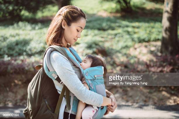 Pretty young mom carrying baby in a baby carrier strolling in the park joyfully.