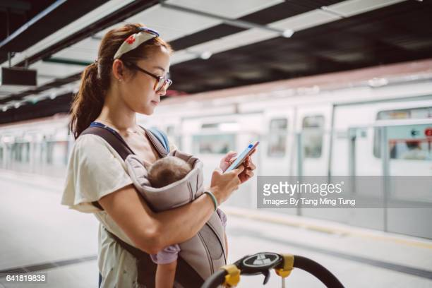 Pretty young mom carrying baby in a baby carrier using smartphone on the train platform